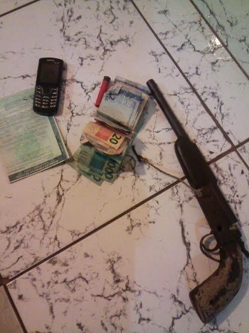 Dinheiro roubado em posto de combustível e arma utilizada no crime.